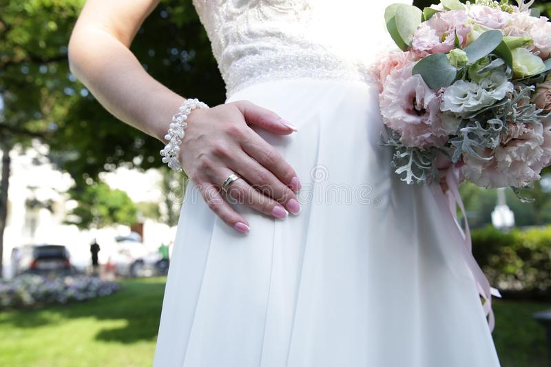 Beautiful bride`s hand with a wedding ring and a white bracelet made from beads lies on a white lace dress and a bouquet stock image