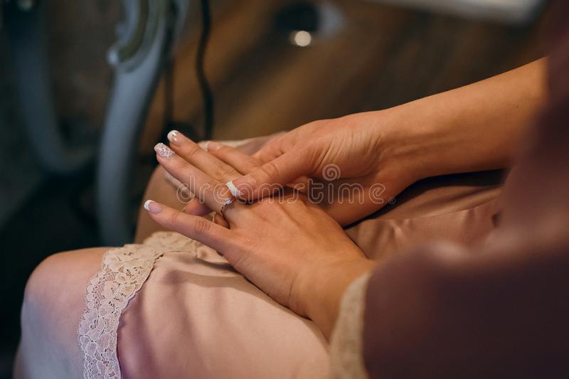 Beautiful bride`s hands on the dress. Fingers with golden rings. Wedding morning.  royalty free stock image