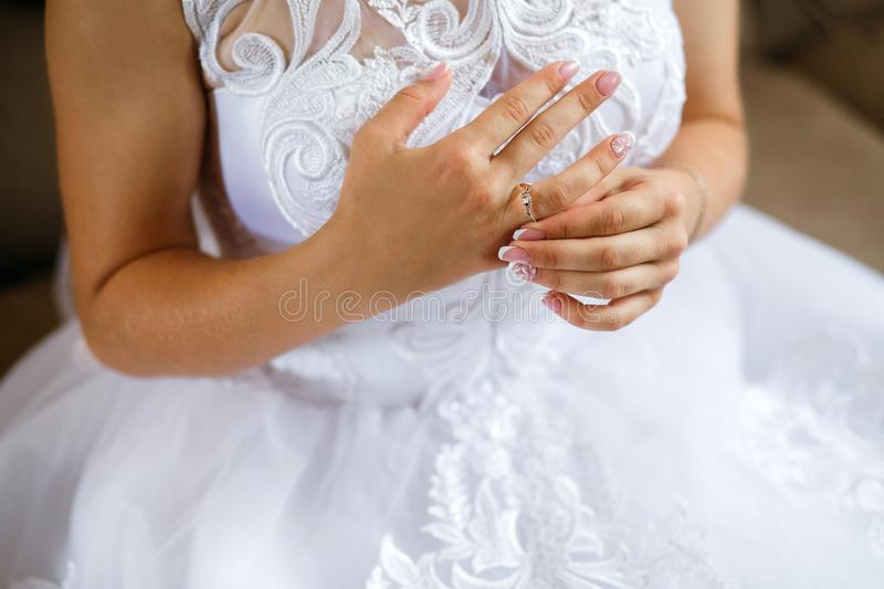 Beautiful bride`s hands on the dress. Fingers with golden rings. Wedding morning.  stock image