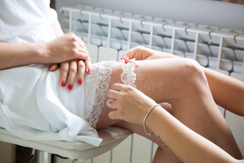 Beautiful bride s leg with white garter. Beautiful bride`s leg with white garter. soft focus royalty free stock photos