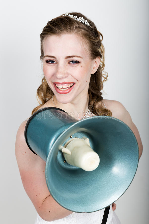 Beautiful bride screaming into a bullhorn. Wedding day. funny bride concept.  royalty free stock images