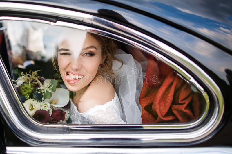 Beautiful bride shows tongue sitting in the car stock photo