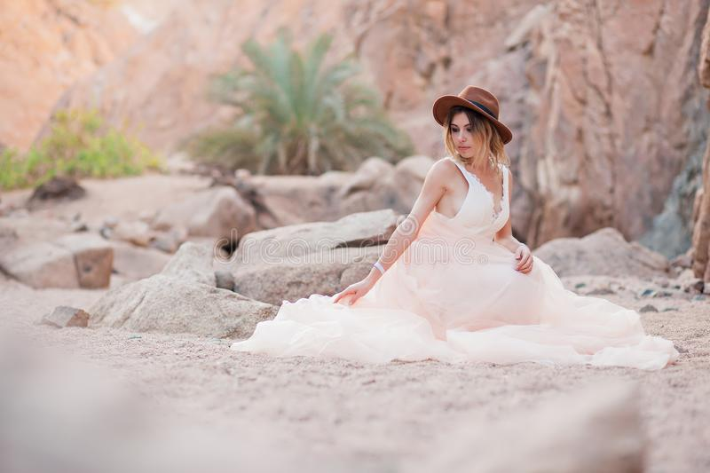 Beautiful bride sits on a stone in a canyon. And straightens her dress stock photography
