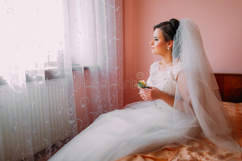 Beautiful bride sitting on a bed near the window in dreams of married life and holding cute little wedding boutonniere royalty free stock images