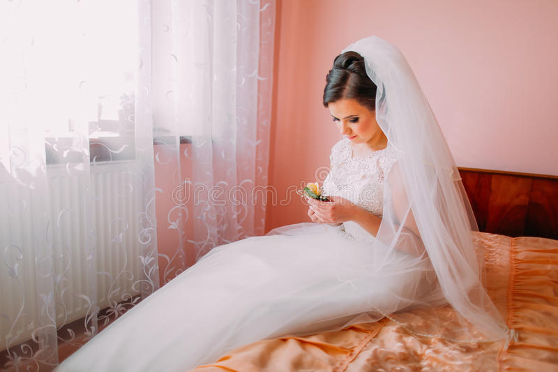Beautiful bride sitting on a bed near the window in waiting and holding cute little wedding boutonniere stock images