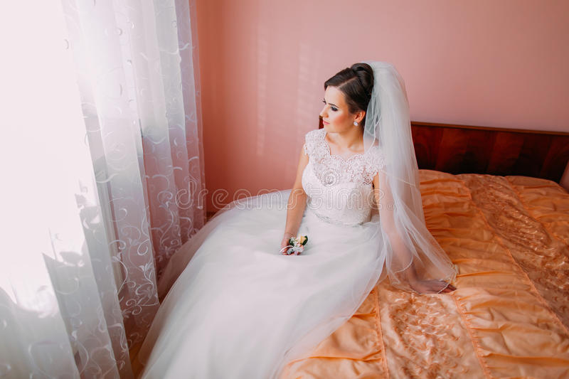 Beautiful bride sitting on a bed in waiting and holding cute little wedding boutonniere royalty free stock photos