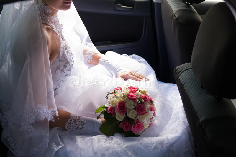 Beautiful bride sitting in the car. Alone royalty free stock image