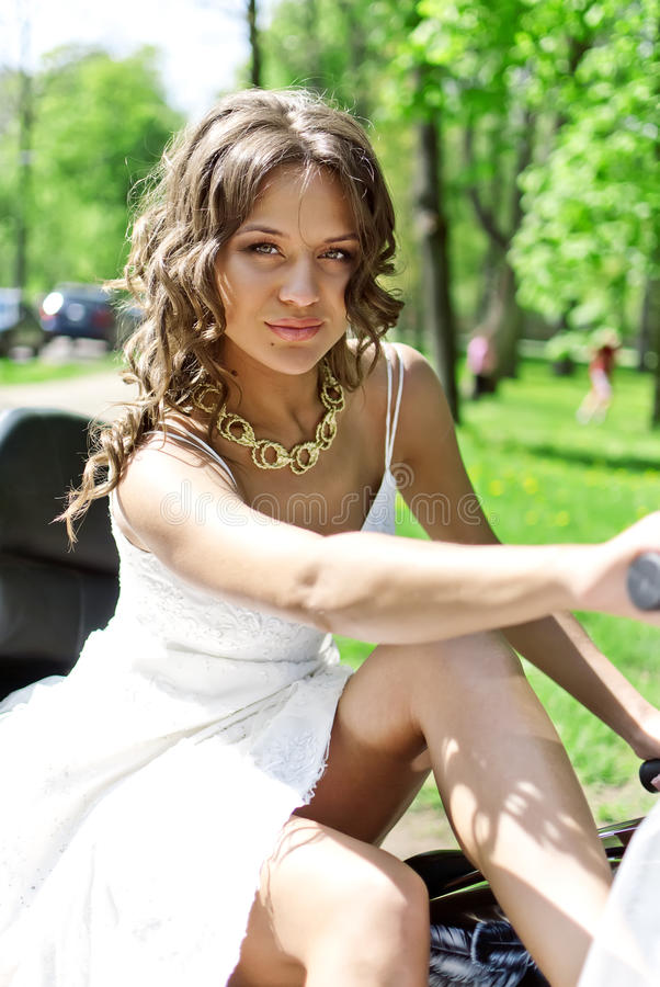 Beautiful bride sitting on a motorcycle stock images