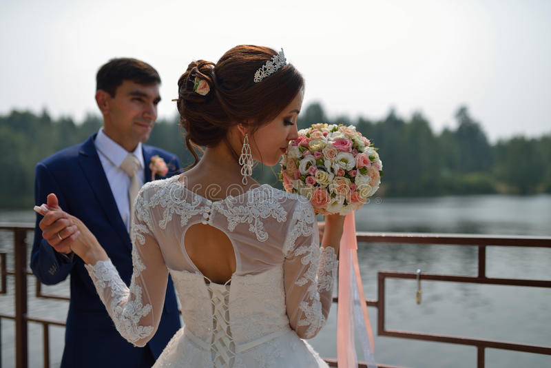 Beautiful bride is smelling wedding bouquet, stylish groom holding her hand at background royalty free stock image