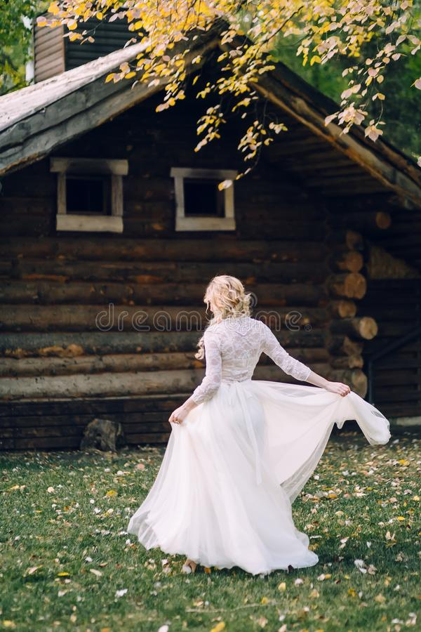 The Beautiful bride is spinning around herself in fluttering dress on wooden house background. Back view. Artwork royalty free stock photography