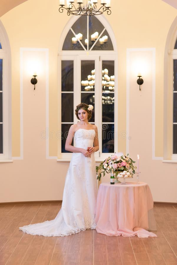 Beautiful bride standing in a light room. stock photo