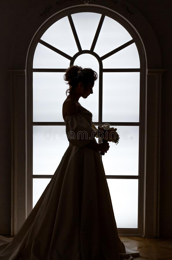 Beautiful bride stands silhouette near window stock photo
