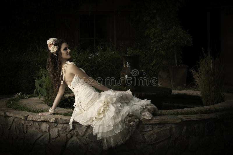 Beautiful bride in strapless vintage wedding dress reclining next to a courtyard fountain royalty free stock image