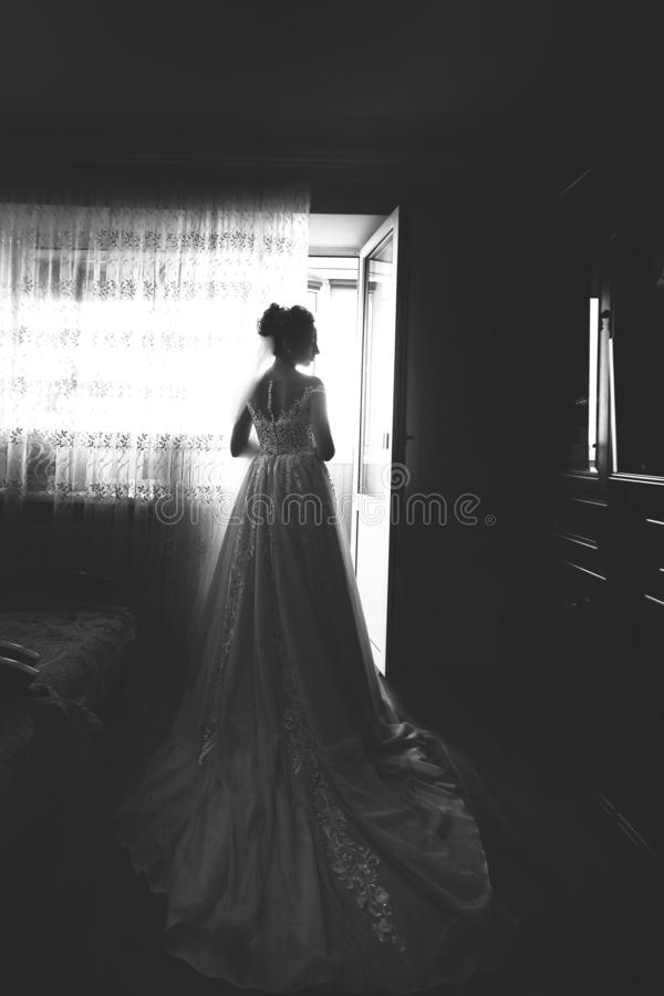 Beautiful bride style. Wedding girl stand in luxury wedding dress near window. Black and white.  stock images