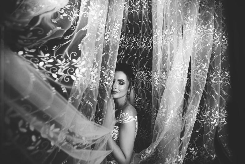 Beautiful bride style. Wedding girl stand in luxury wedding dress near window. Black and white royalty free stock photos