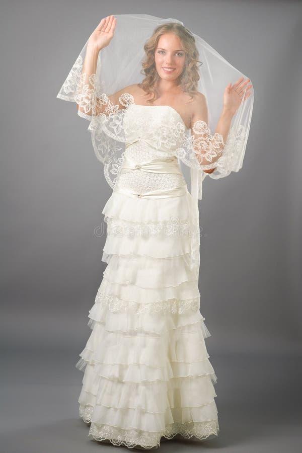 Beautiful bride under veil posing in studio