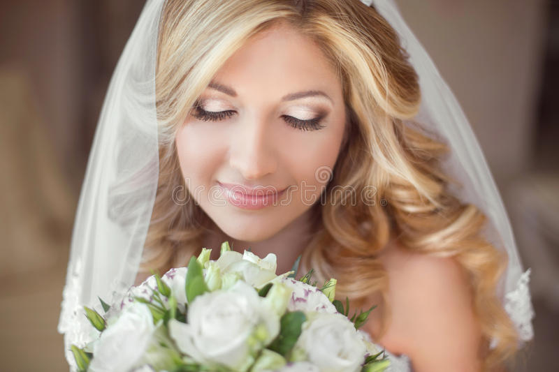 Beautiful bride with wedding bouquet of flowers. Makeup. Blond c. Urly hairstyle. Smiling young woman stock image