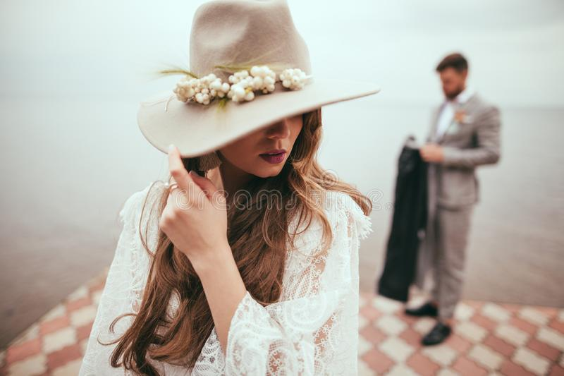 beautiful bride in wedding dress and hat in boho style on pier at lake groom stock images