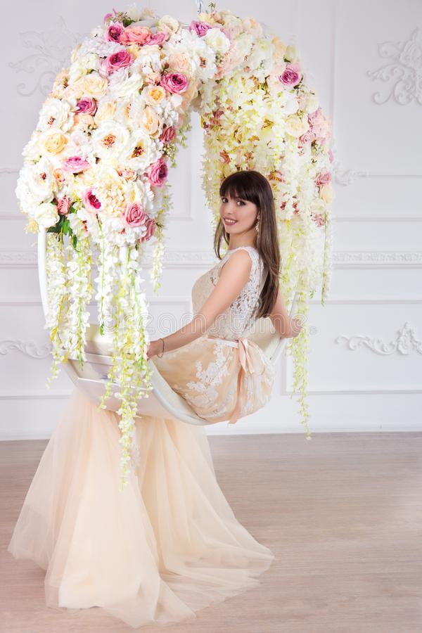 Beautiful bride in a wedding dress in a chic interior in a studio. A beautiful bride in a wedding dress in an interior sits on a hanging circle in floral stock image