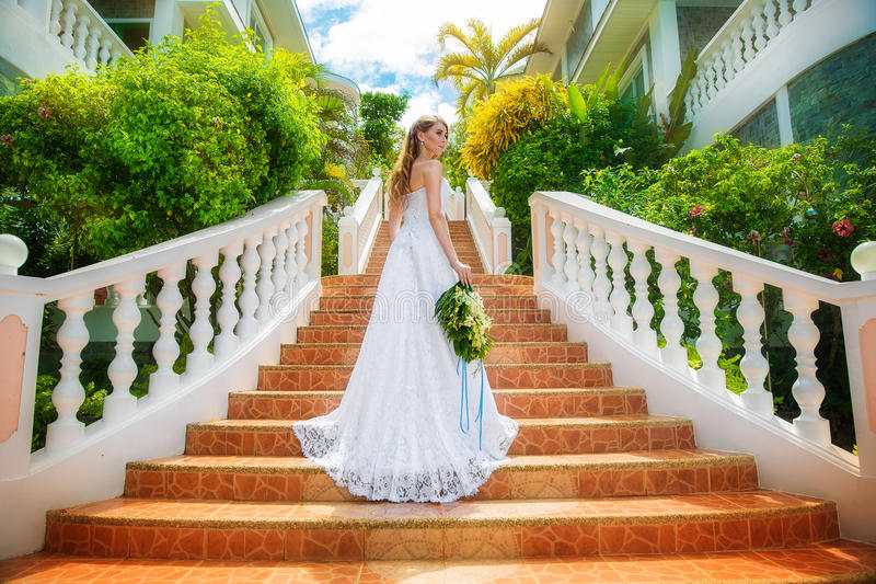 Beautiful bride in wedding dress with long train standing on the royalty free stock photography