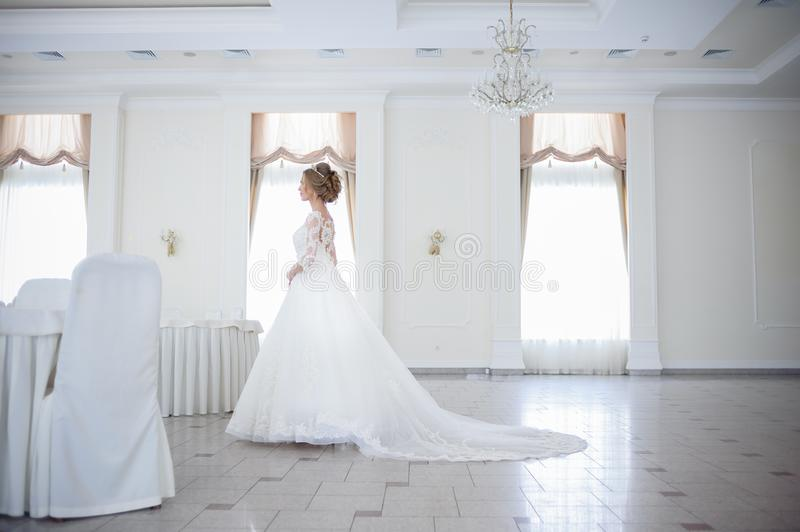Beautiful bride in a wedding dress in a luxurious white room with a large chandelier royalty free stock image
