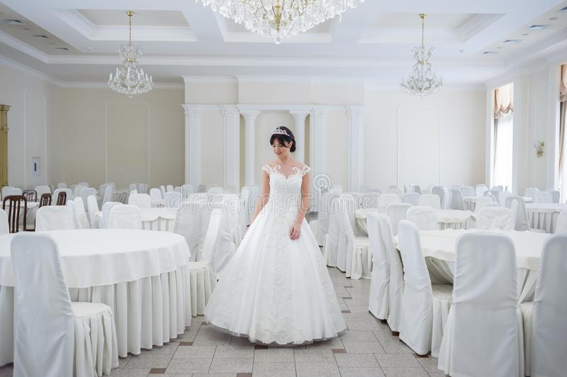 Beautiful bride in a wedding dress in a luxurious white room with a large chandelier stock image