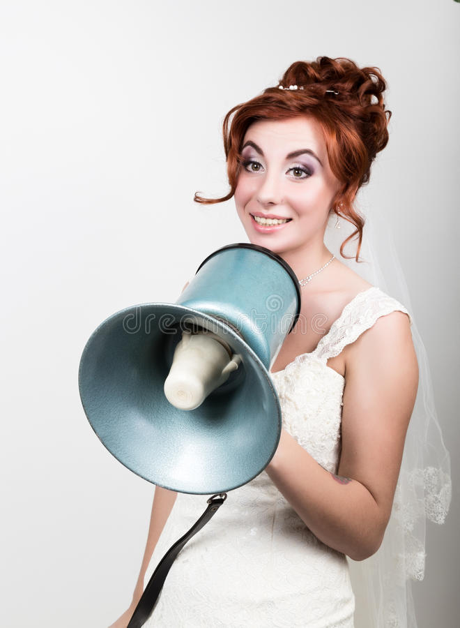 Beautiful bride in wedding dress with makeup and hairstyle, she yells into a bullhorn. Public Relations. Beautiful bride in a wedding dress with a wedding makeup stock image