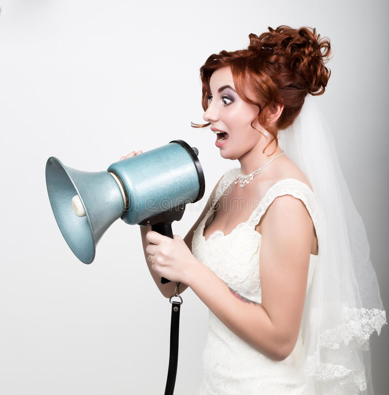 Beautiful bride in wedding dress with makeup and hairstyle, she yells into a bullhorn. Public Relations. Beautiful bride in a wedding dress with a wedding makeup royalty free stock photography