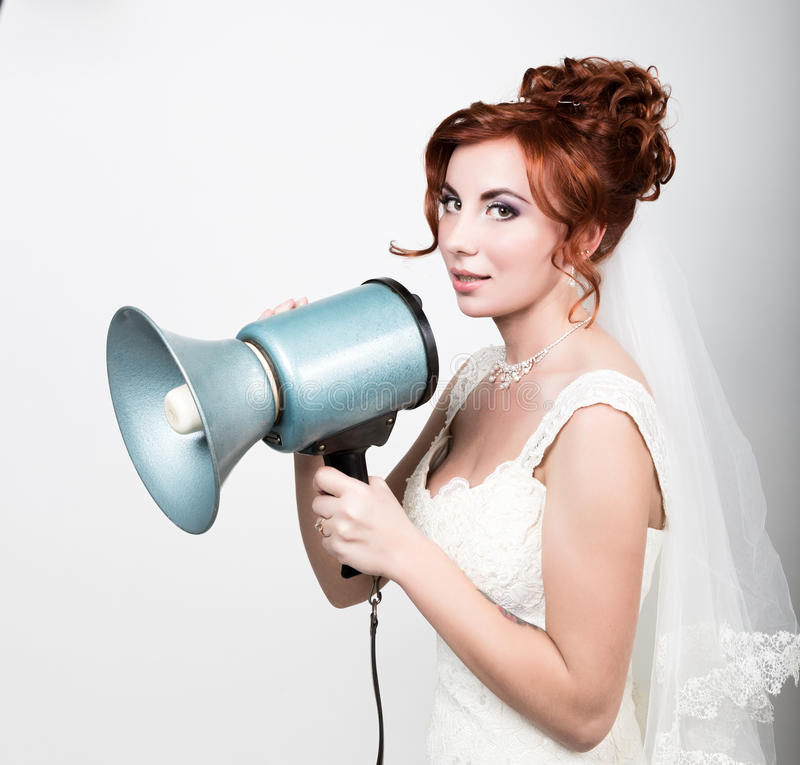 Beautiful bride in wedding dress with makeup and hairstyle, she yells into a bullhorn. Public Relations. Beautiful bride in a wedding dress with a wedding makeup royalty free stock photos