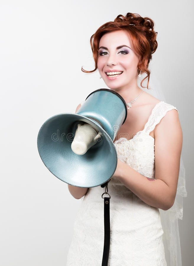 Beautiful bride in wedding dress with makeup and hairstyle, she yells into a bullhorn. Public Relations. Beautiful bride in a wedding dress with a wedding makeup royalty free stock images
