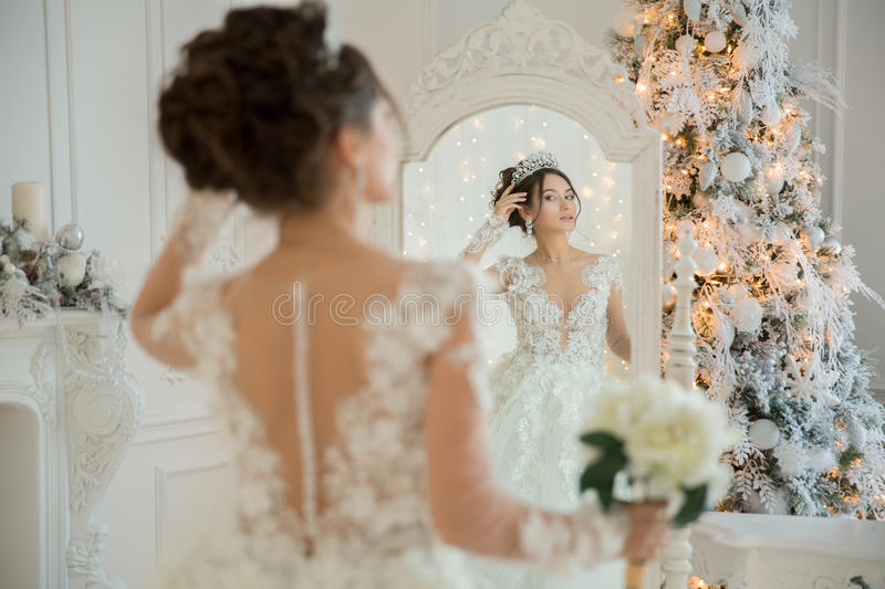 Beautiful bride in a wedding dress at a mirror in Christmas. Girl repeats the hairstyle and makeup. royalty free stock photos