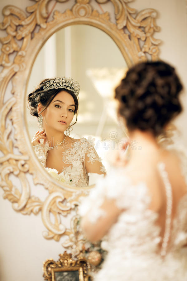 Beautiful Bride In A Wedding Dress At A Mirror In Christmas. Gir ...