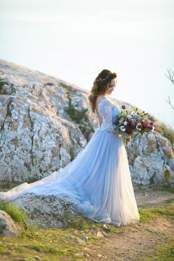 Beautiful bride in wedding dress on the mountain top. Stunning young bride with curly hair and a bouquet of flowers in stock images