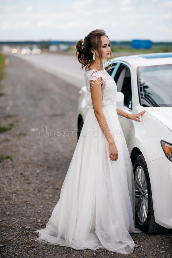 A beautiful bride in a wedding dress is standing next to a white car by the road stock image