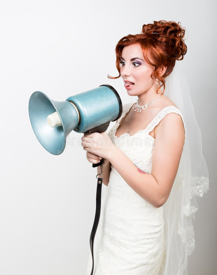 Beautiful bride in a wedding dress with a wedding makeup and hairstyle, she yells into a bullhorn. Public Relations.  stock images
