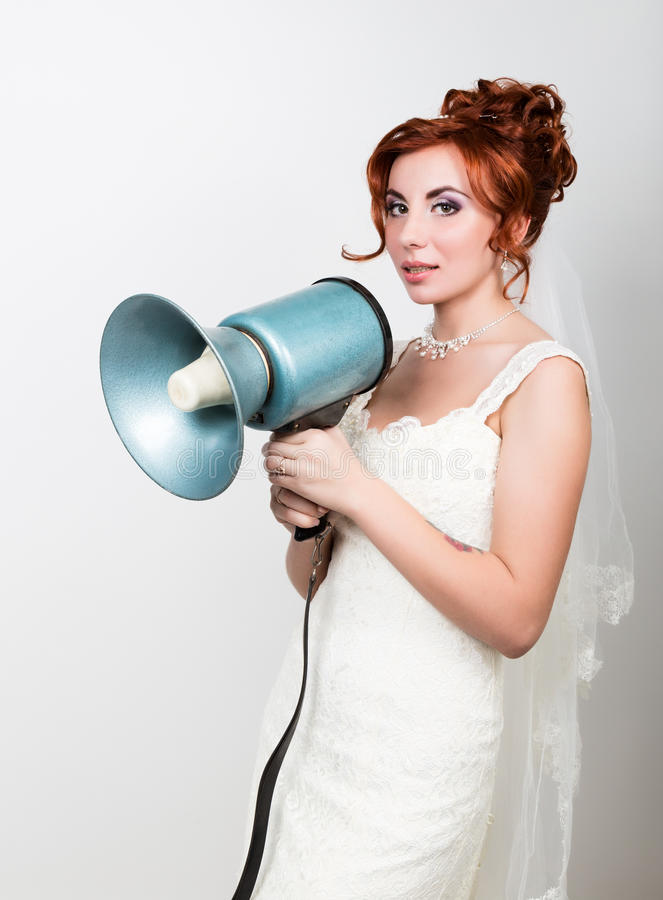 Beautiful bride in a wedding dress with a wedding makeup and hairstyle, she yells into a bullhorn. Public Relations.  royalty free stock images