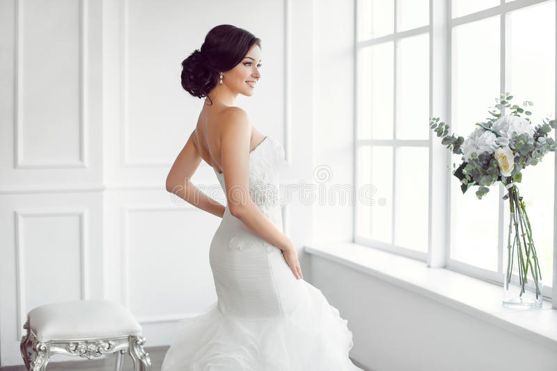 Beautiful bride. Wedding hairstyle make-up luxury fashion dress concept. Beauty portrait of wearing fashion wedding dress with feathers with luxury delight make royalty free stock photography