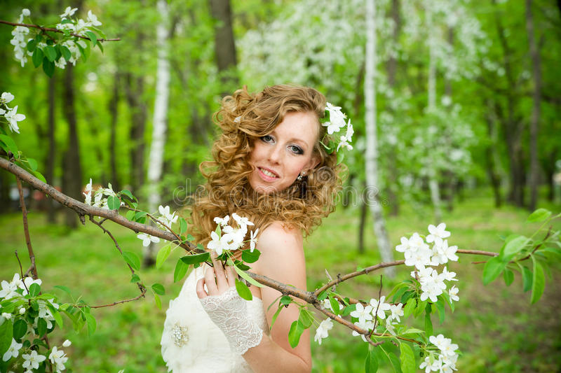 Beautiful bride in a white dress in blooming gardens in the spring. Professional make-up and hairstyle stock photo