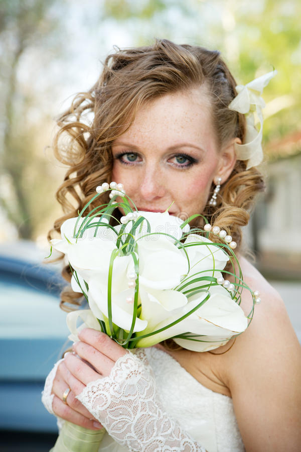 Beautiful bride in a white dress with a bouquet of calla lilies royalty free stock photography