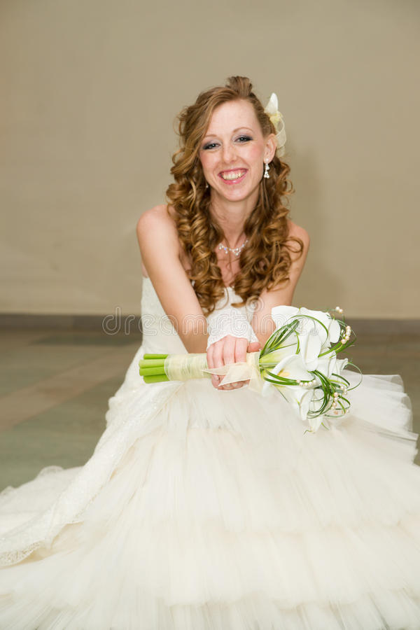 Beautiful bride in a white dress with a bouquet of calla lilies stock image