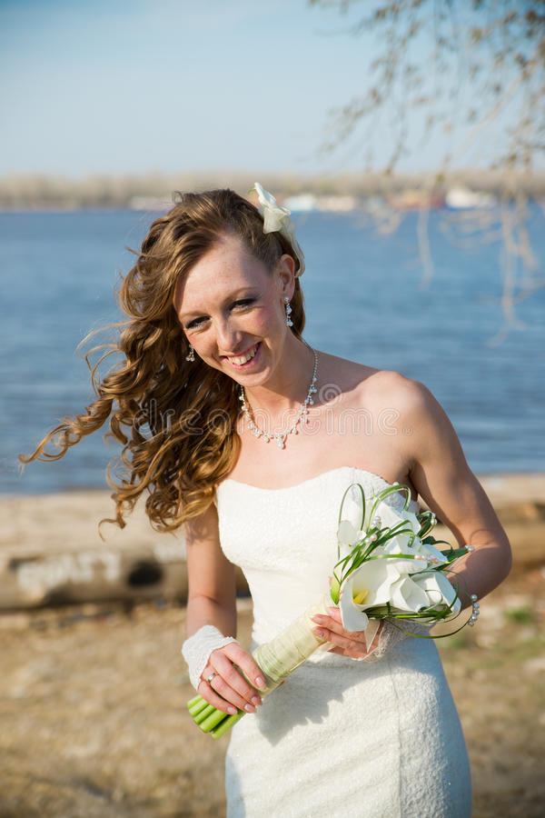 Beautiful bride in a white dress on coast of river royalty free stock images