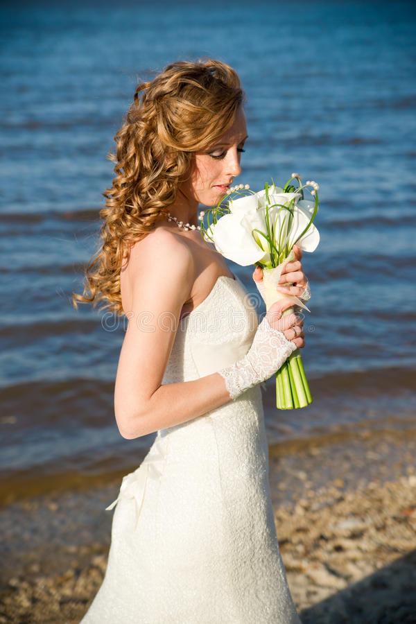 Beautiful bride in a white dress on coast of river royalty free stock image