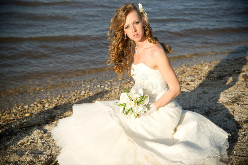 Beautiful bride in a white dress on coast of river royalty free stock photo