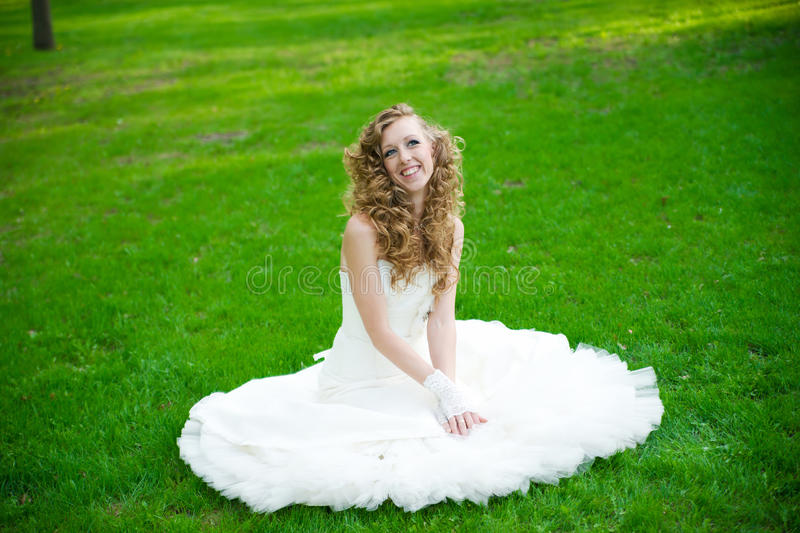 Beautiful bride in a white dress on green grass in summer royalty free stock photo