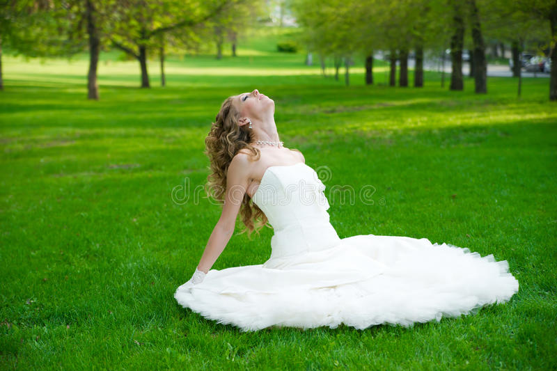 Beautiful bride in a white dress on green grass in summer royalty free stock image