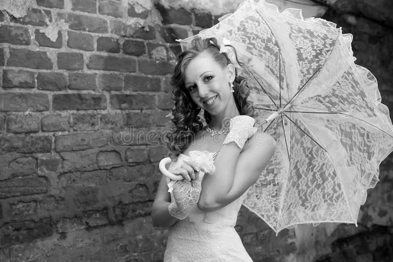Beautiful bride in white dress with umbrella royalty free stock images