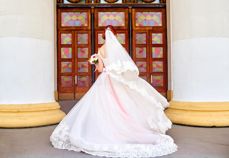 Beautiful bride in white dress and veil with wedding bouquet royalty free stock images