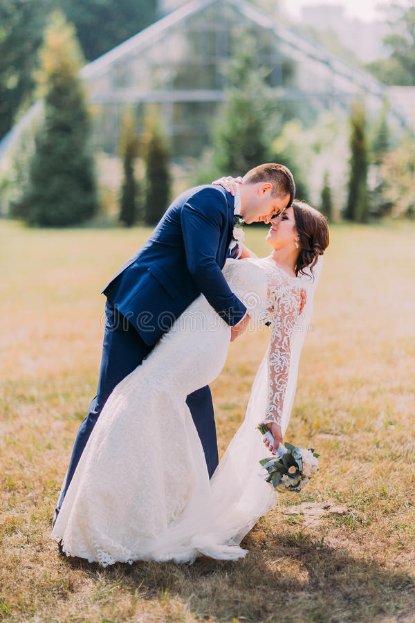 Beautiful bride with white wedding dress and groom in stylish blue suit posing outdoor on lawn. Greenhouse at background royalty free stock photo