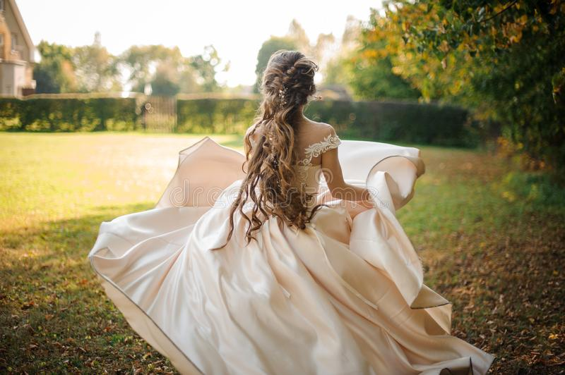 Beautiful bride in a white wedding dress running in the park stock image
