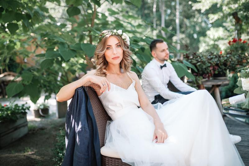 A beautiful bride in a white wedding dress and wreath sits on a chair next to the groom, resting. And preparing for a happy family life stock images